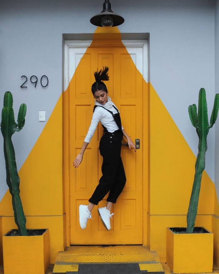 A woman is jumping in front of a yellow wall