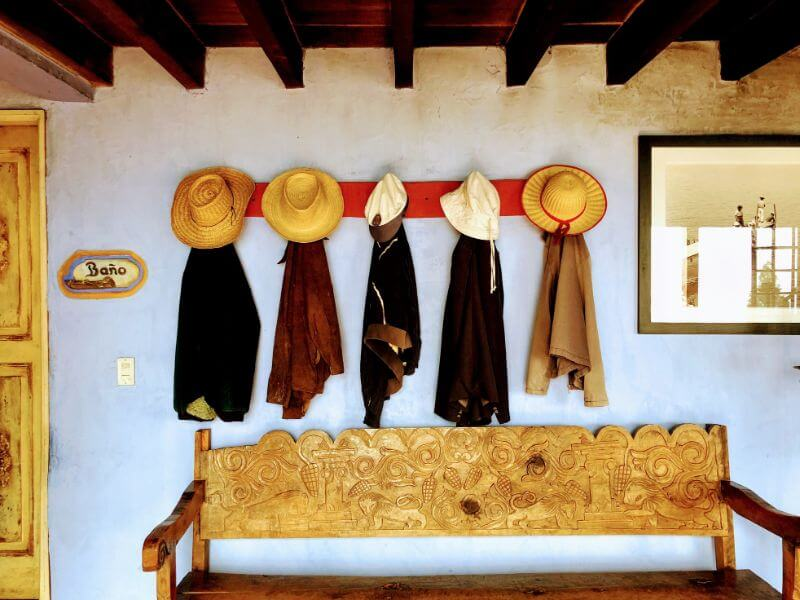 Five cowboy hats and cloaks on the wall