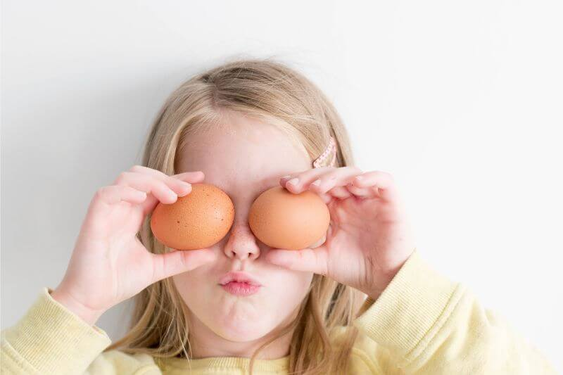 Girl hiding her eyes with eggs