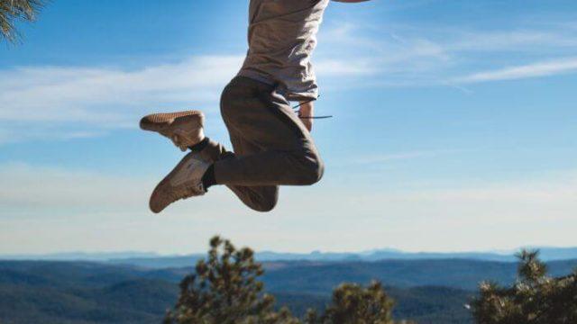 Shirtless men jumping in the mountains