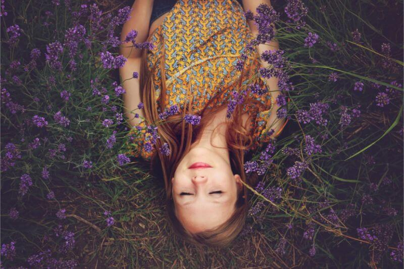 Sleeping woman surrounded by lavender on the grass
