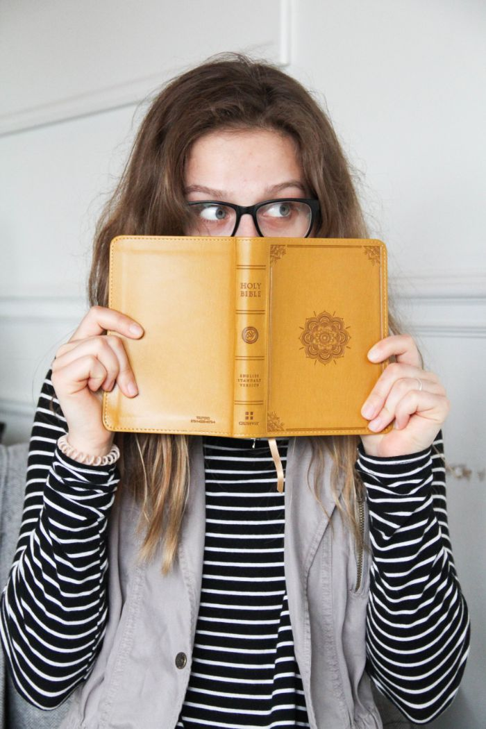 Woman hiding her face in a yellow book