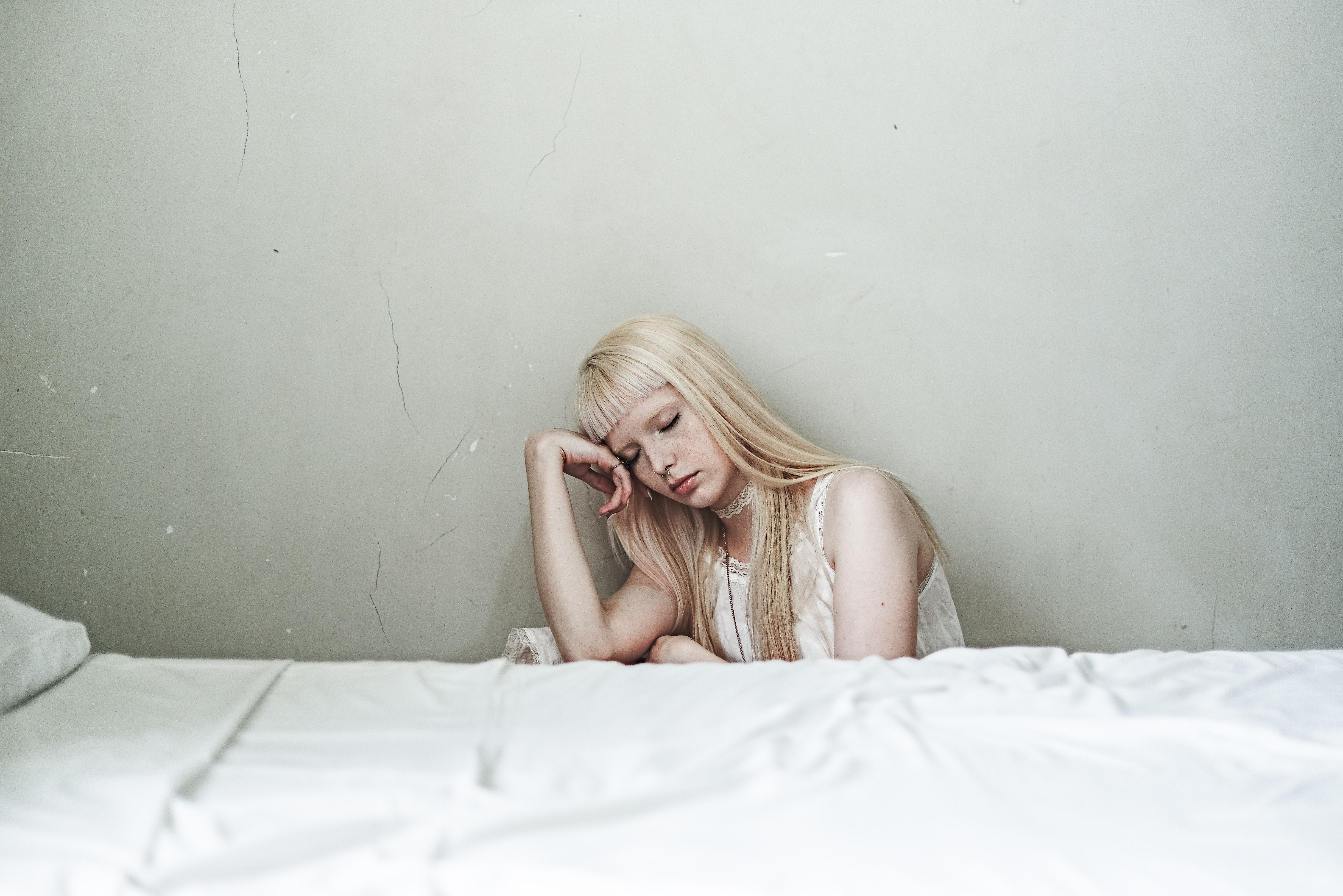 ベッドの横で悩む白人女性