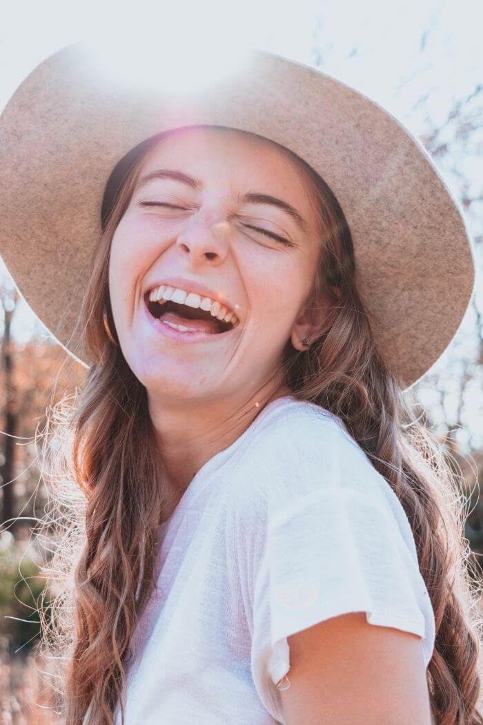 Full-faced smiling girl wearing a straw hat