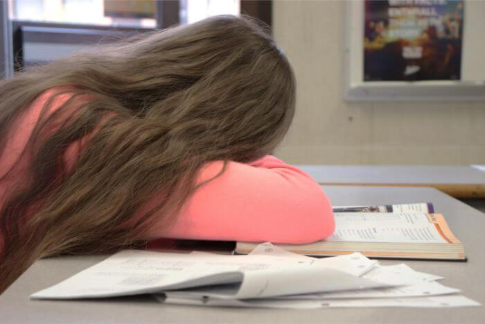Girl in pink clothes is lying on the desk