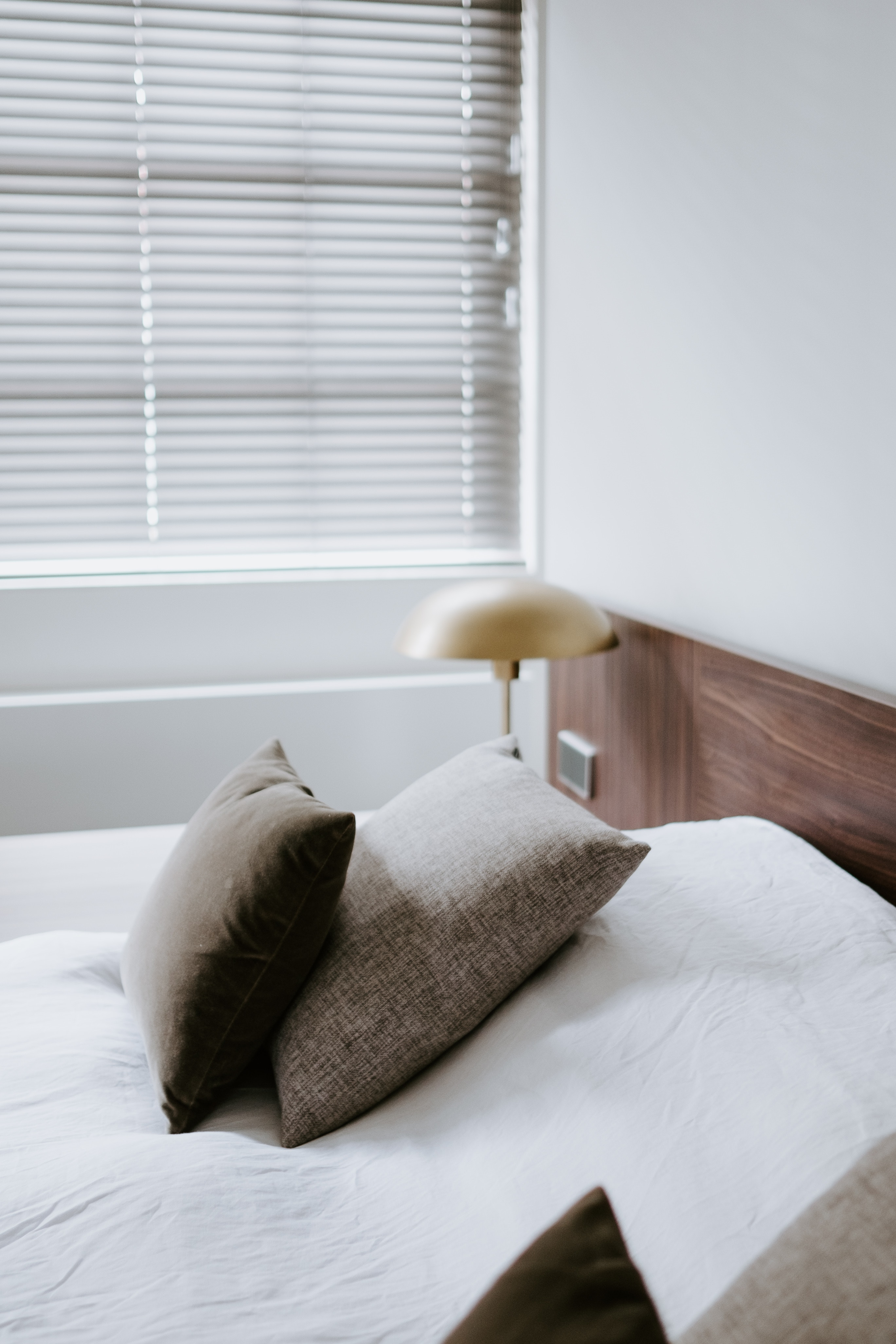 bed with pillows near Venetian blinds