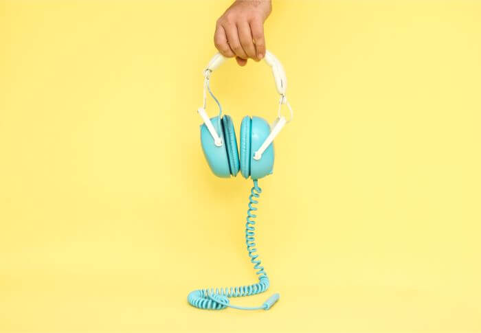 Holding blue headphones in one hand in front of a yellow back