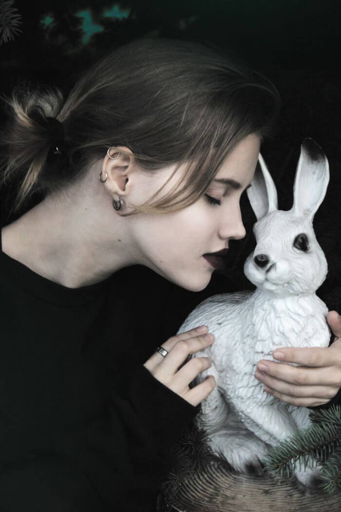 woman hugging white rabbit figurine