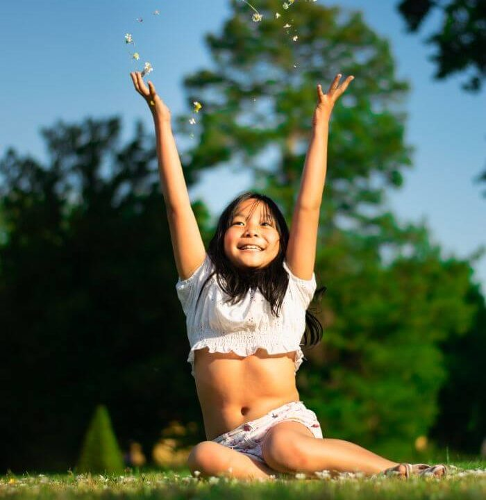 girl sitting on grass throwing flowers in the air