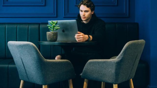 man sitting on couch with looking at his MacBook on table