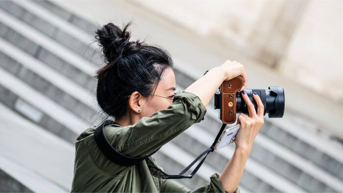woman holding black DSLR camera and taking picture at daytime