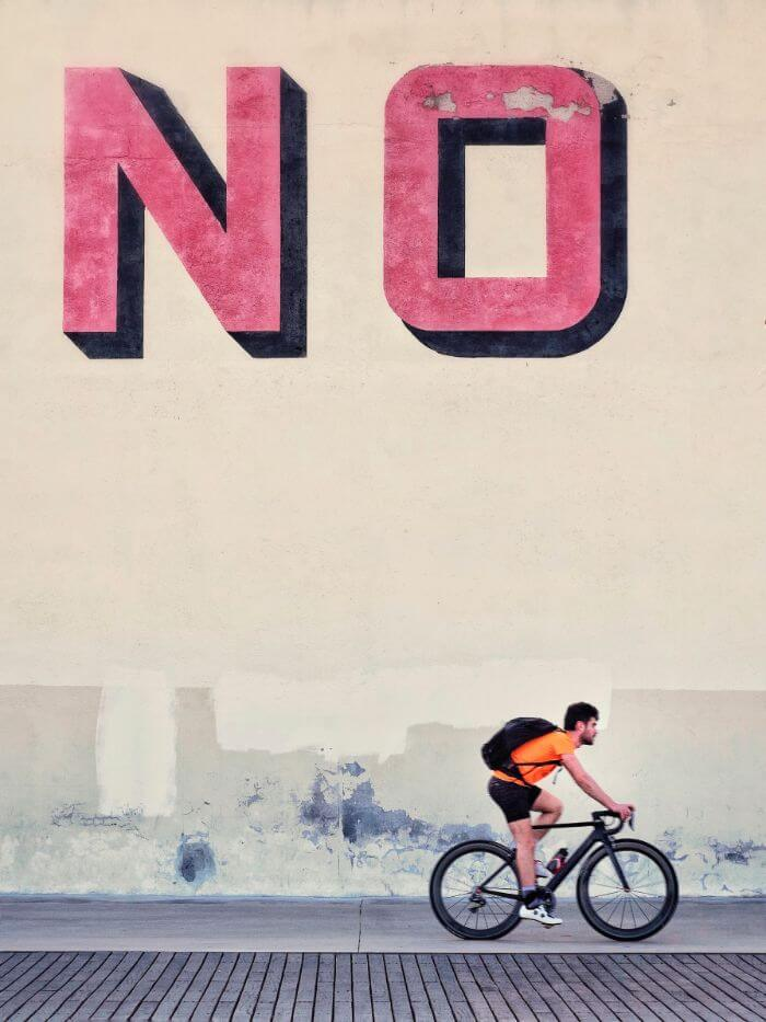 A bicycle that passes in front of a wall that is clearly marked NO