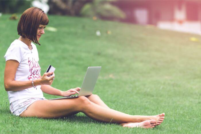 A woman sitting with a PC on her leg on the grass