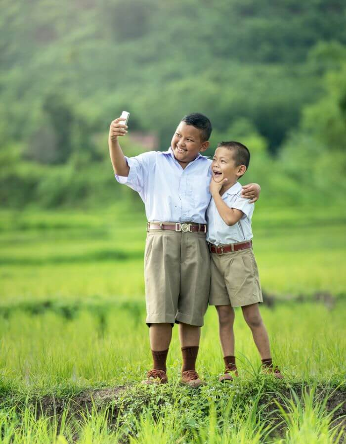Two boys taking selfies in the rice field