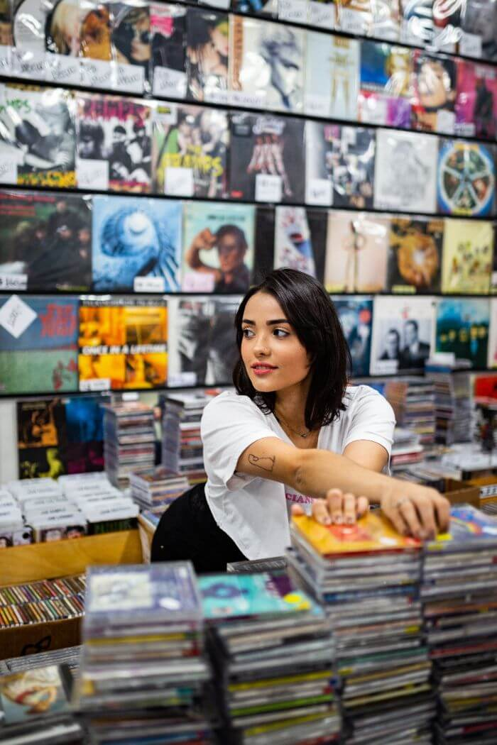 Woman in a white shirt relaxing at the record shop