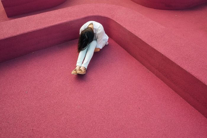 Depressed woman on red floor