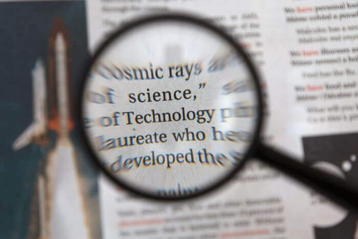 Magnifying a newspaper with a magnifying glass