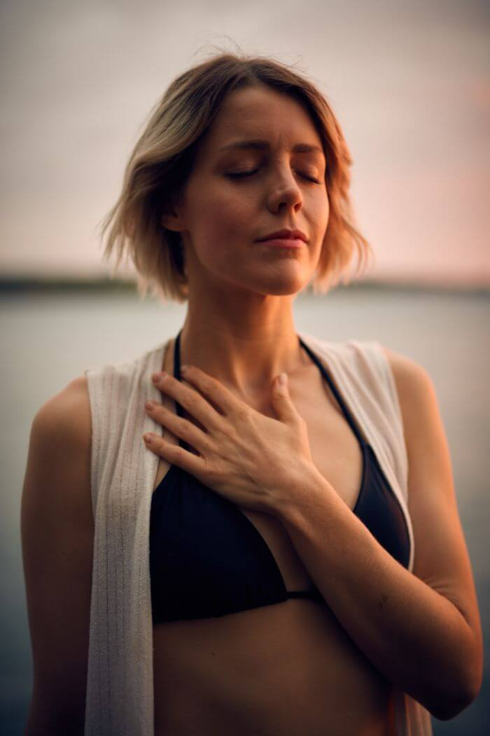 Woman closes her eyes with one hand on her chest