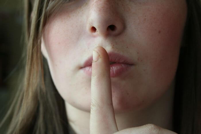 Woman face with index finger on lips