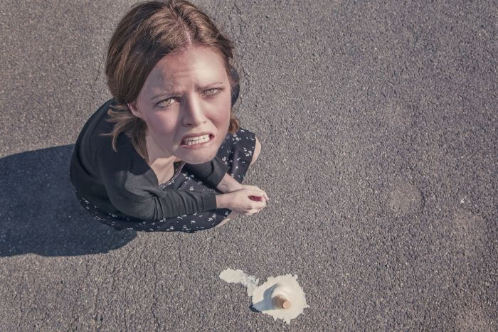 Woman with crying face as soft ice cream on ground