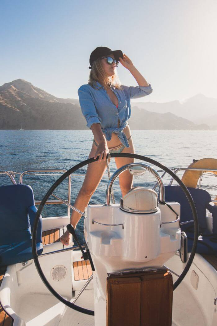 woman standing in front of captains wheel